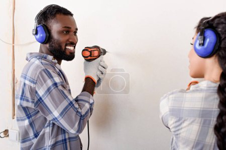 happy young man drilling wall and looking at girlfriend while making renovation of home