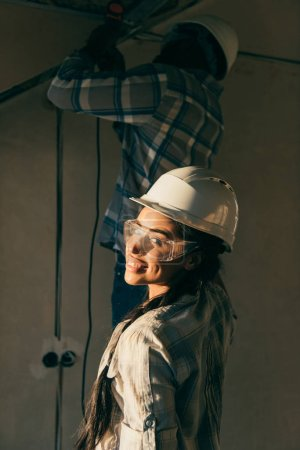 happy young woman in hard hat looking at camera while her husband making renovation of home