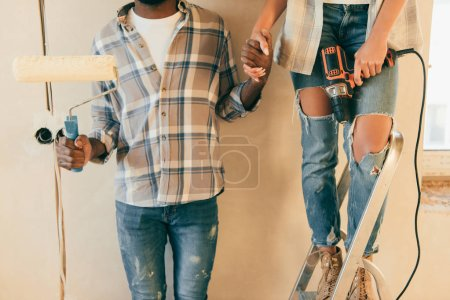 cropped shot of couple with rolling brush and drill making renovation of home