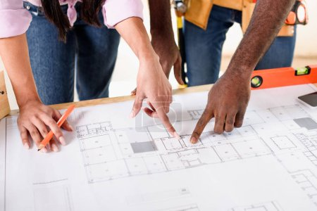 cropped shot of couple pointing at building plan while making renovation of home