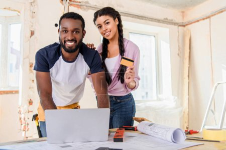 smiling young couple using laptop for e-shopping while making renovation of home