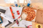 top view of box with pizza, tools and smartphone with youtube app on screen on building plan