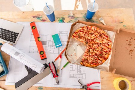 top view of box with pizza, tools and smartphone with twitter app on screen on building plan