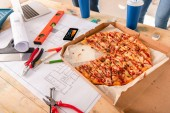 close-up shot of box with pizza, tools and smartphone with graphs on screen on building plan