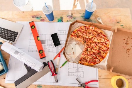 top view of box with pizza, tools and smartphone on building plan