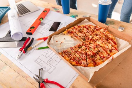 Photo for Close-up shot of box with pizza, soda drinks, tools and smartphone on building plan - Royalty Free Image