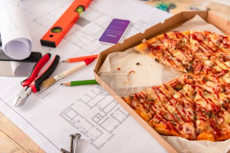 close-up shot of box with pizza, tools and smartphone with instagram app on screen on building plan