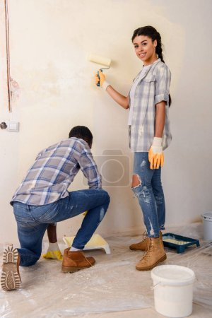 young couple painting walls together during renovation of home