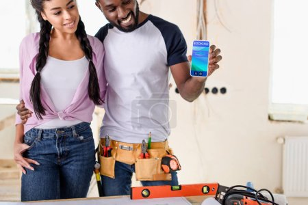 couple holding smartphone with booking app on screen during renovation