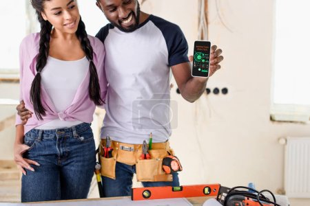 couple holding smartphone with charts on screen during renovation