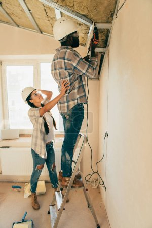 side view of man in hard hat and goggles working with power drill on ladder while his girlfriend standing near during renovation of home