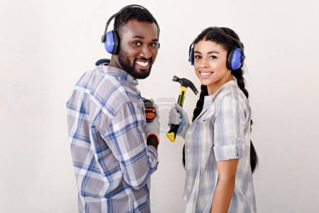 smiling young african american couple in protective headphones standing with drill and hammer during renovation of new home