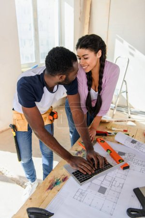 Photo for High angle view of young couple using laptop and looking at each other during renovation of home - Royalty Free Image