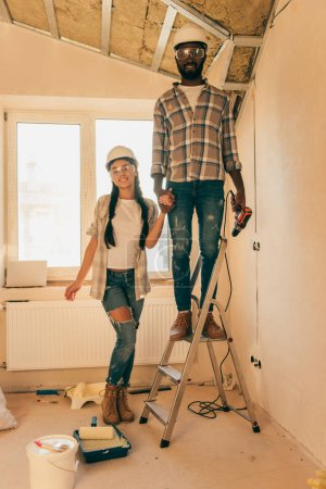 african american man in hard hat and goggles standing with power drill on ladder while his girlfriend standing near during renovation of home