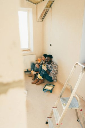 high angle view of african american couple drinking beer during renovation at home