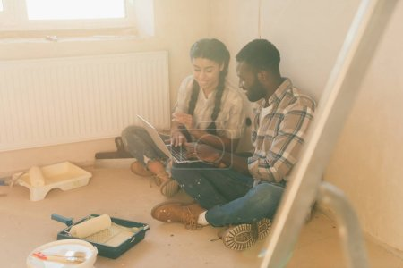 Photo for Young smiling couple using laptop during renovation of new home - Royalty Free Image