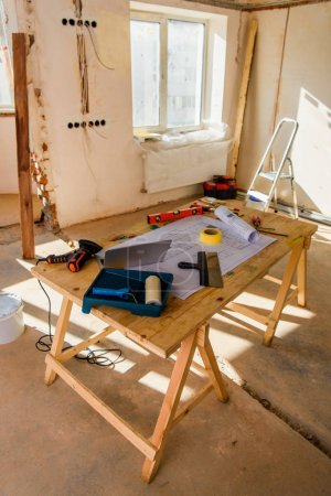 high angle view of room with table with blueprint and laptop during renovation of home