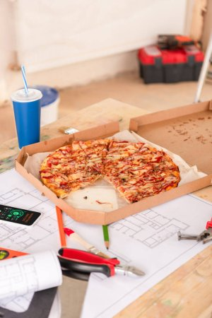 selective focus of pizza, soda, blueprint, tools and smartphone with charts on screen on table