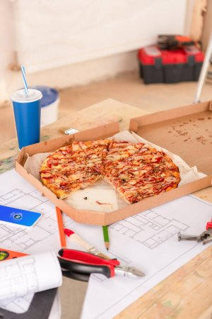 selective focus of pizza, soda, blueprint, tools and smartphone with shazam on screen on table