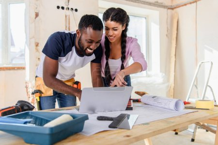 young african american woman pointing at laptop screen to boyfriend during renovation of home