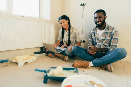 Photo for African american couple resting with laptop during renovation of new home - Royalty Free Image