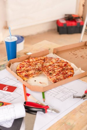 selective focus of pizza, soda, blueprint, tools and smartphone with youtube on screen on table