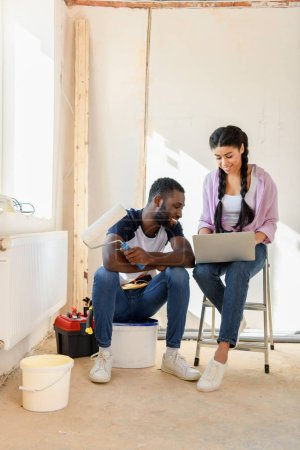 Photo for Happy african american couple with laptop and paint roller during renovation of home - Royalty Free Image
