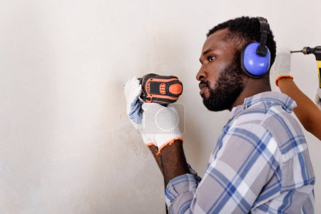 side view of thoughtful african american man in protective headphones working with power drill at home