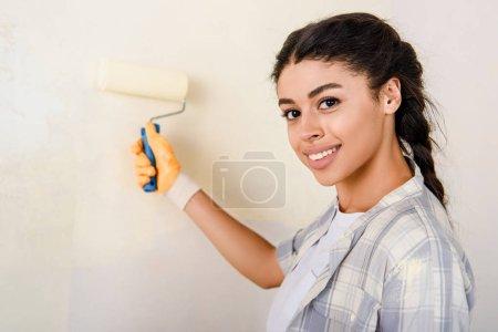 Photo pour Mise au point sélective du mur peinture heureuse femme afro-américaine - image libre de droit