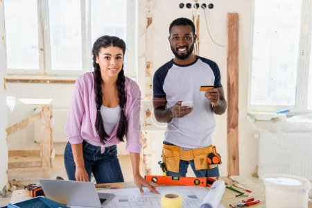 young african american man with credit card and smartphone standing near girlfriend during renovation of home