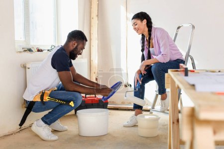 happy young man sitting near bucket with paint while his girlfriend sitting with paint roller during renovation at home
