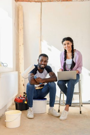 Photo for Smiling african american couple with laptop and paint roller looking at camera during renovation of home - Royalty Free Image