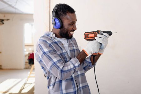 side view of laughing young african american man in protective headphones and gloves having fun with power drill during renovation of home