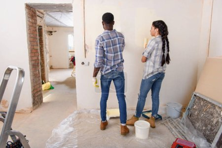rear view of african american couple painting wall by paint rollers at new home
