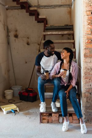 Photo for Smiling african american couple resting with disposable cups of coffee during renovation at new home - Royalty Free Image