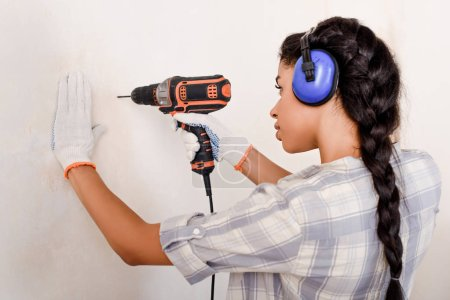 focused african american woman in protective headphones and gloves working with power drill