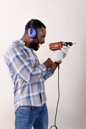 happy young african american man in protective headphones and gloves having fun with power drill