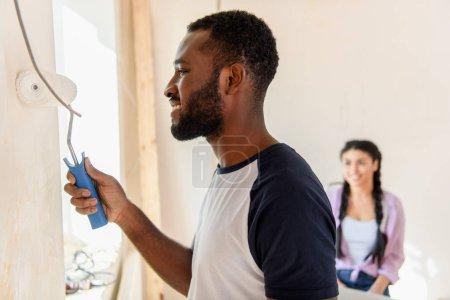 Photo pour Vue latérale du mur peinture heureux homme afro-américain de rouleau à peinture tandis que sa copine assis derrière à la maison - image libre de droit