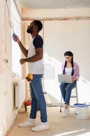Photo pour Vue latérale du mur peinture afro-américain alors que sa petite amie à l'aide de portable derrière pendant la rénovation de la maison - image libre de droit