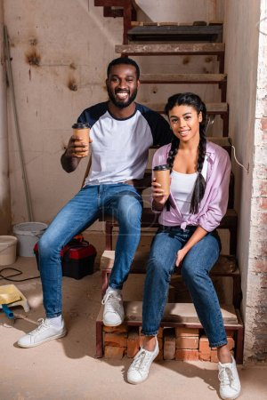 happy african american couple resting with disposable cups of coffee during renovation at new home