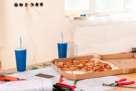 selective focus of pizza, soda, blueprint, tools and smartphone with blank screen on table