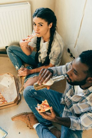 high angle view of african american couple eating pizza and drinking beer during renovation at home