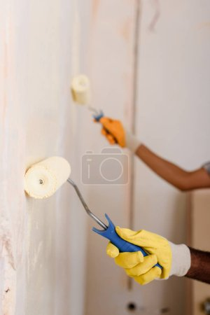 cropped image of couple painting wall by paint rollers at new home