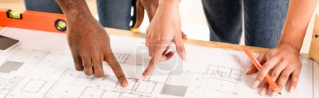 cropped image of couple pointing by finger at blueprint