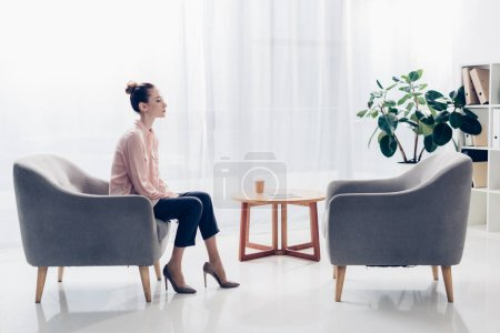 side view of beautiful businesswoman sitting in armchair in office and looking away