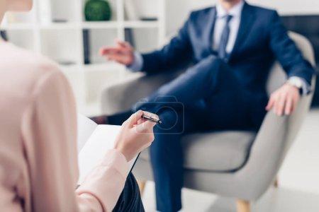 Photo pour Image recadrée d'un homme d'affaires donnant une interview à un journaliste en fonction - image libre de droit