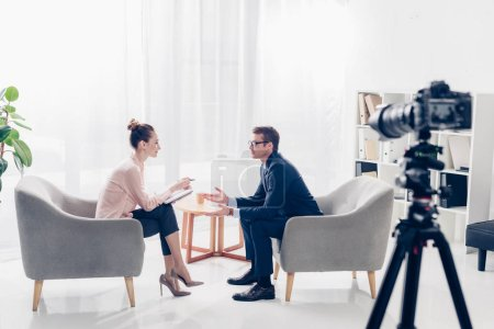 handsome businessman giving interview to journalist in office, they sitting in armchairs and looking at each other