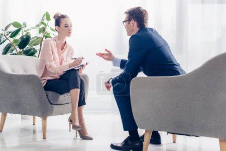 Photo pour Bel homme d'affaires donnant une interview à un journaliste au bureau, ils sont assis dans des fauteuils et se regardent - image libre de droit