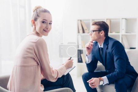 Photo pour Journaliste joyeux prendre des notes pendant l'entrevue avec un homme d'affaires au bureau et en regardant la caméra - image libre de droit
