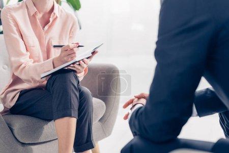 Photo pour Image recadrée d'un journaliste prenant des notes lors d'une interview avec un homme d'affaires au bureau - image libre de droit